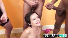 Short haired babe blowing long cocks in bukkake